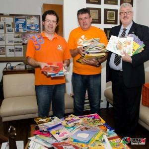 Osni Mongruel Junior e Jacob Cavagnari, do Colégio Sepam, realizam a entrega dos livros ao coordenador do Pegaí, Idomar Augusto Cerutti